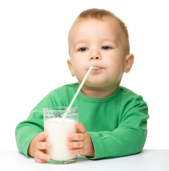 Cute little boy is drinking milk using straw while sitting at table, isolated over white