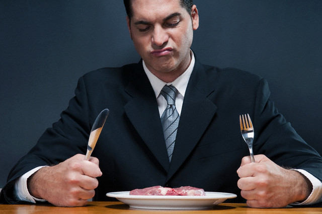Businessman frowning at a raw steak --- Image by © Glowimages/Corbis